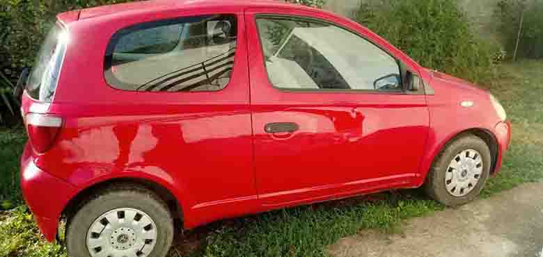 Desni bočni prikaz crvenog automobila Toyota Yaris
