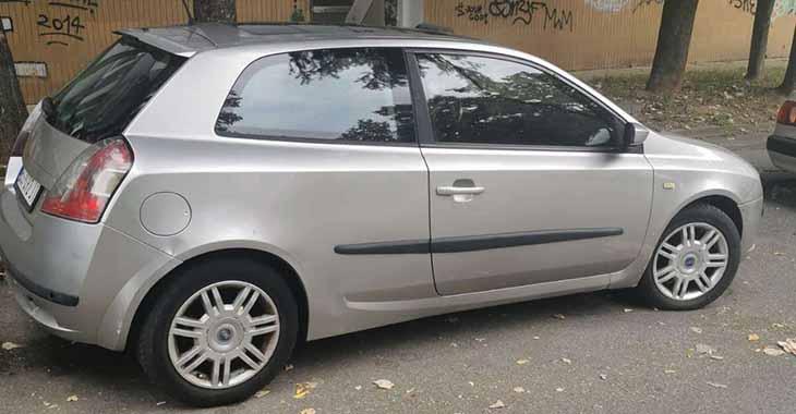 Desni bočni prikaz sivog automobila Fiat Stilo na parkingu