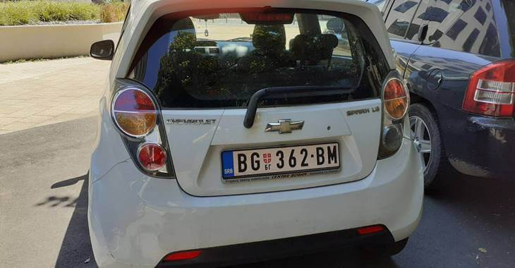Zadnji prikaz belog automobila Chevrolet Spark