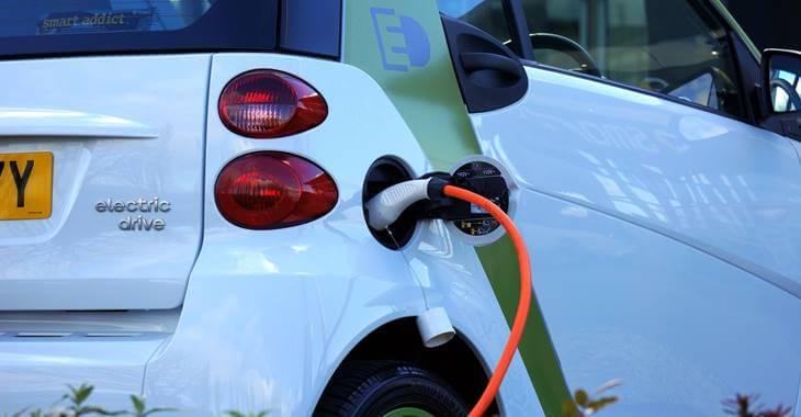 prikaz belog električnog automobila na punjaču